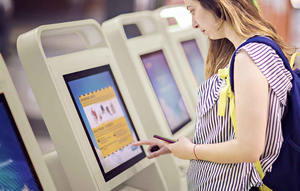 Young woman touching interactive screen to check in online